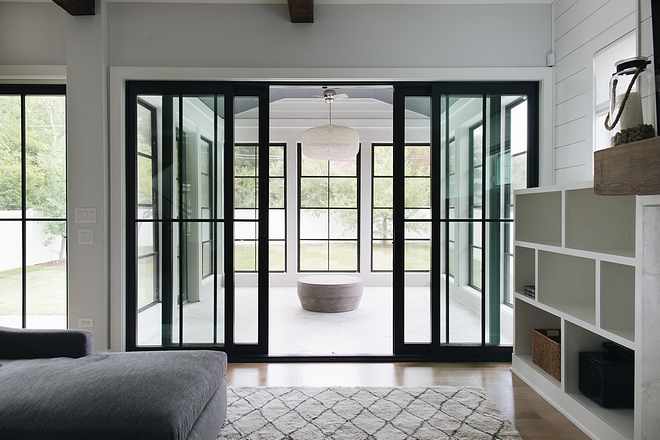 The family room opens to a spacious sunroom with black steel doors and windows #sunroom #blacksteeldoors #blacksteelwindows