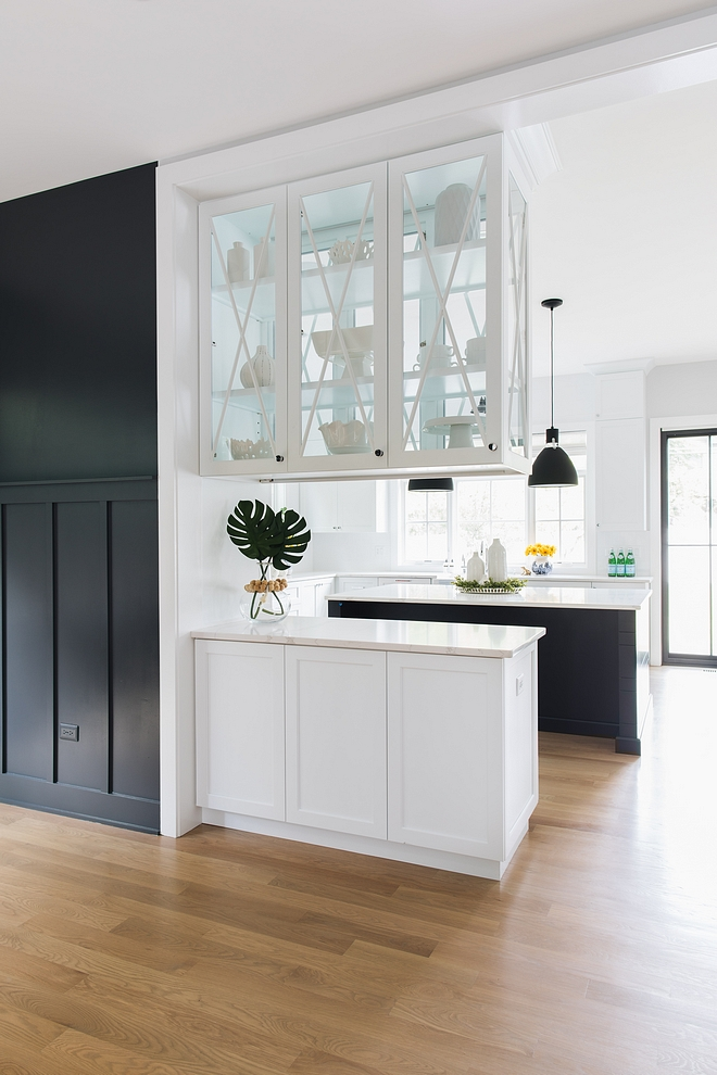 The upper cabinets feature glass doors on both sides, allowing more natural light into the dining room and easy access from either room