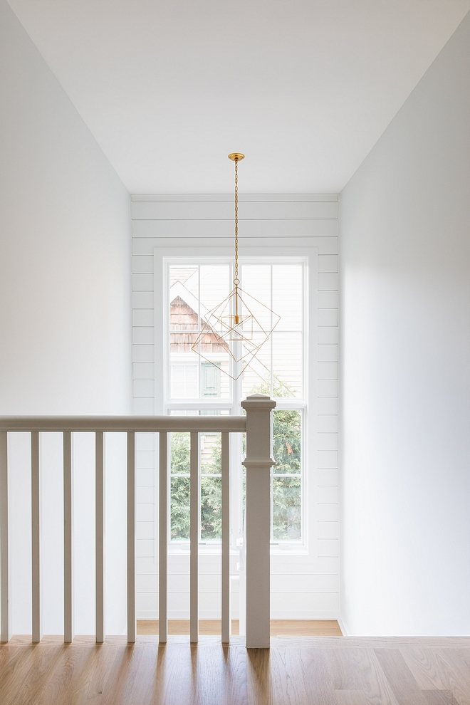 The staircase also features shiplap on an accent wall, framing a tall window Millwork is painted in Sherwin Williams Extra White #staircaseshiplap #staircase #shiplap #Sherwinwilliamsextrawhite #tallwindows