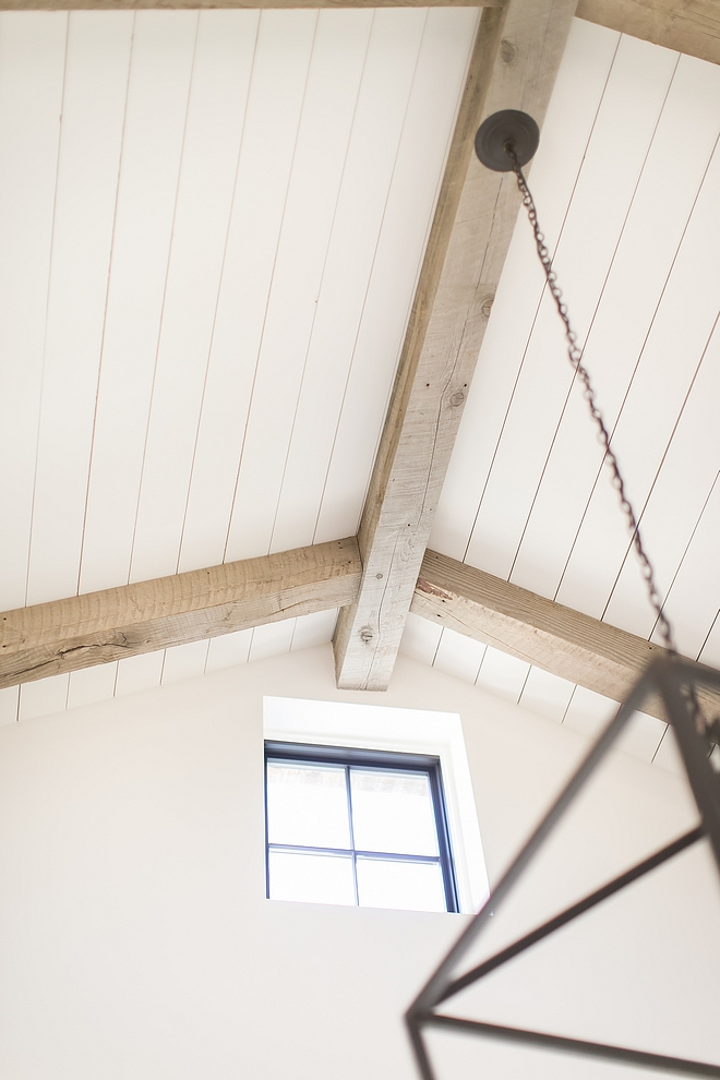 Plank Ceiling Ceiling is clad with white planking and reclaimed beams #PlankCeiling #Ceiling #beams
