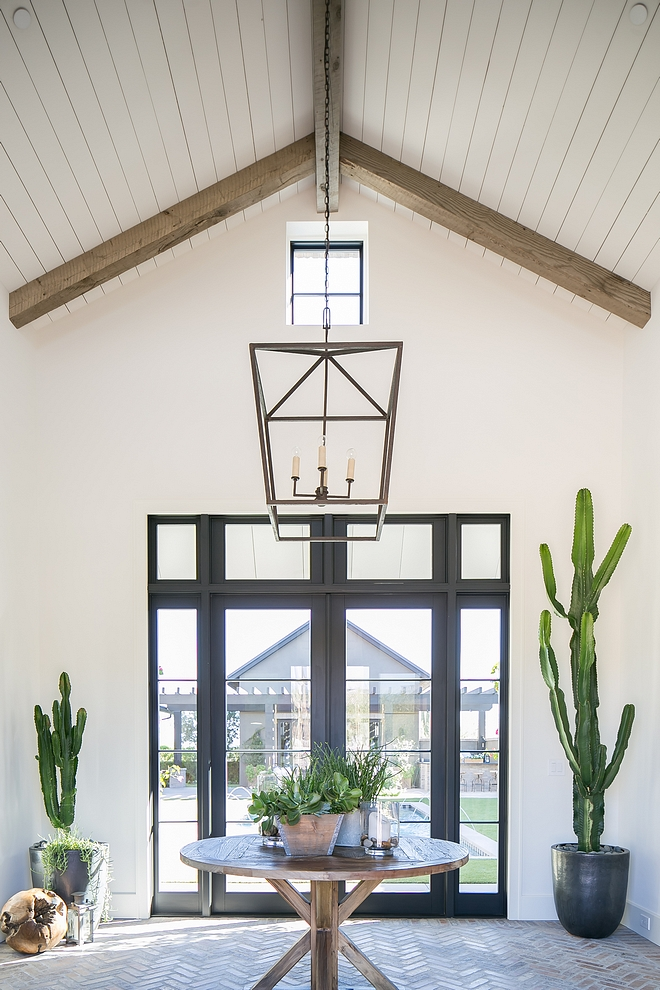Foyer Steel Door Foyer featuring Steel and glass door, herringbone brick flooring, vaulted ceiling with plank and reclaimed beams #foyer #steelDoor #herringbonebrick #plank #vaultedceiling #reclaimedbeams