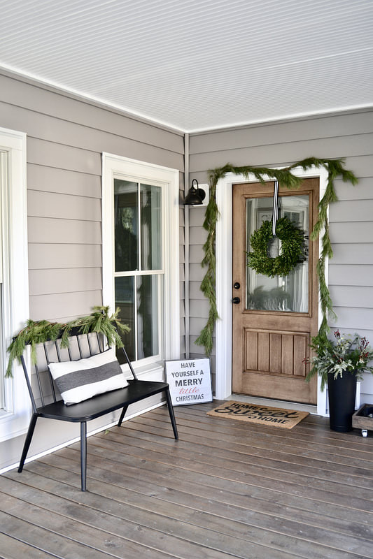 Farmhouse Porch Christmas Decor Farmhouse Porch Christmas Decor with Black spindle bench and garland and wreath on front door Farmhouse Porch Christmas Decor #FarmhousePorch #PorchChristmasDecor
