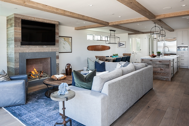 The living room features a fireplace with reclaimed plank boards Ceiling treatment is a combination of drywall and reclaimed wood wrapped false beams #fireplace #reclaimedboards #reclaimedwood #reclaimedplanks #falsebeams