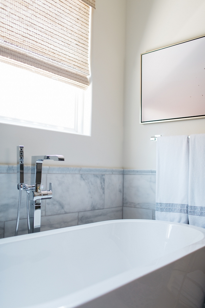 The sleek tub is bordered with large format marble tiles. The marble tiles are laid horizontally for a polished feel. For another special detail, we capped the large wall tile with a chair rail. It adds a nice, finished edge to the space