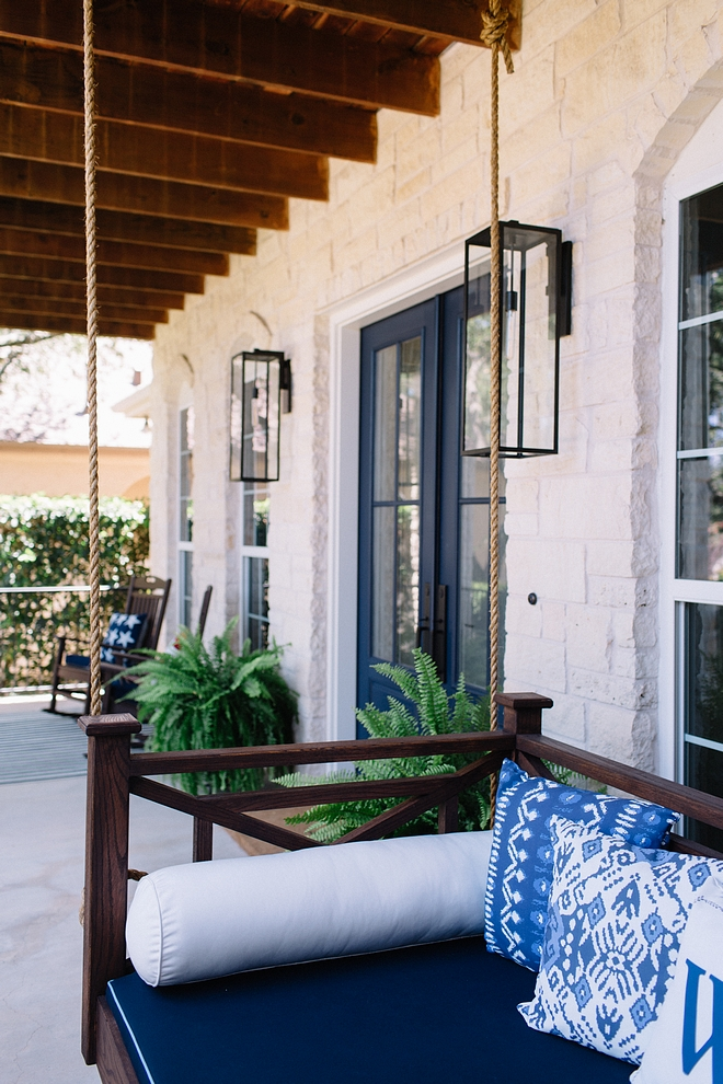 Porch Swing We installed a porch swing with navy blue and white accents. The seat is upholstered in a navy fabric with contrast pale blue piping. A mix of patterned pillows add some personality to the front porch. The dark stain wood frame and decorative siding of the bench gives a strong contrast to the front porch swing #porchswing