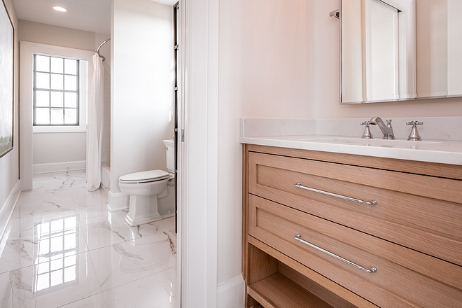 The Jack and Jill bathroom features Rift-Cut White Oak cabinetry with inset drawers, Rift-Cut White Oak Frost Rift-Cut White Oak cabinetry #RiftCutOak #WhiteOak #cabinetry