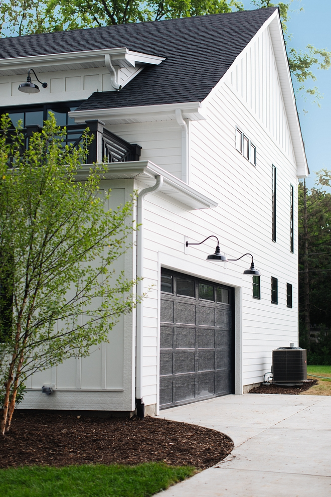 Farmhouse garage Black Garage doors for modern farmhouse The side entry garage - with balcony over it - features black garage door painted in Sherwin Williams SW 7069 Iron Ore #Farmhousestyle #blackgaragedoor #garage #farmhousegarage