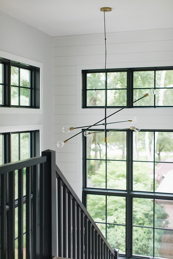 Farmhouse staircase with shiplap paneling, black windows, black railing and a modern mobile chandelier #farmhousestaircase #shiplap #staircaseshiplap #blackwindows #modernchandelier #mobilechandelier