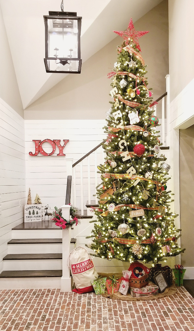 Farmhouse Christmas Tree 12 foot Christmas tree now stands tall in the foyer with brick flooring and shiplap walls The styling is classic farmhouse with little pops of patterns and assortment of reds #FarmhouseChristmasTree #Farmhouse #ChristmasTree #brickflooring #shiplap #brick