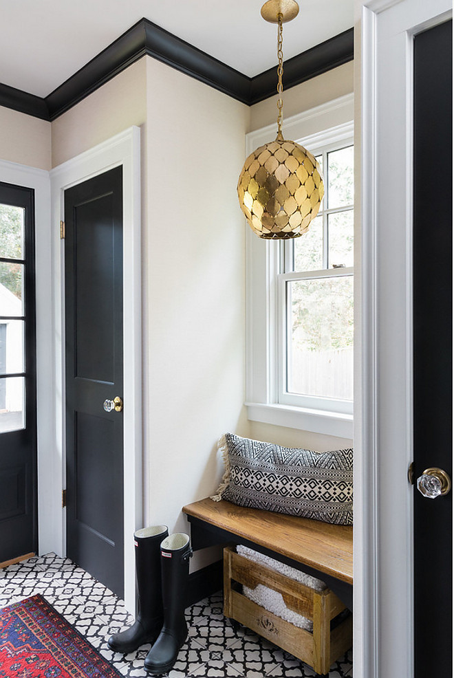 Mudroom features black doors, black trim, black cabinets and back and white cement tile