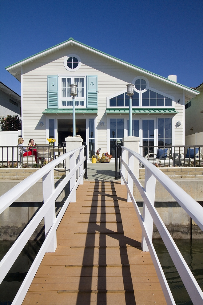 Beach house with turquoise shutters painted in Benjamin Moore wythe blue and seafoam metal roof Coastal vibes