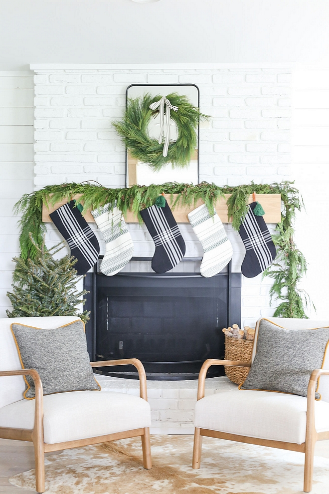 decorated her stunning fireplace with a natural Cedar garland, Cedar wreath and beautiful stockings The homeowner decorated her stunning fireplace with a natural Cedar garland, Cedar wreath and black and white stockings #minimalistchristmas #chirstmas #christmas