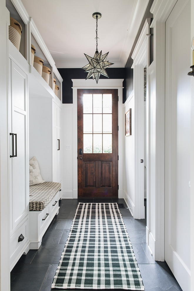 Mudroom with wainscoting, black walls painted in Benjamin Moore Black and built-ins painted in Benjamin Moore Decorators White Flooring is Black Slate Tile and lighting is Moravian Star pendant #mudroom #wainscoting #Benjaminmoore