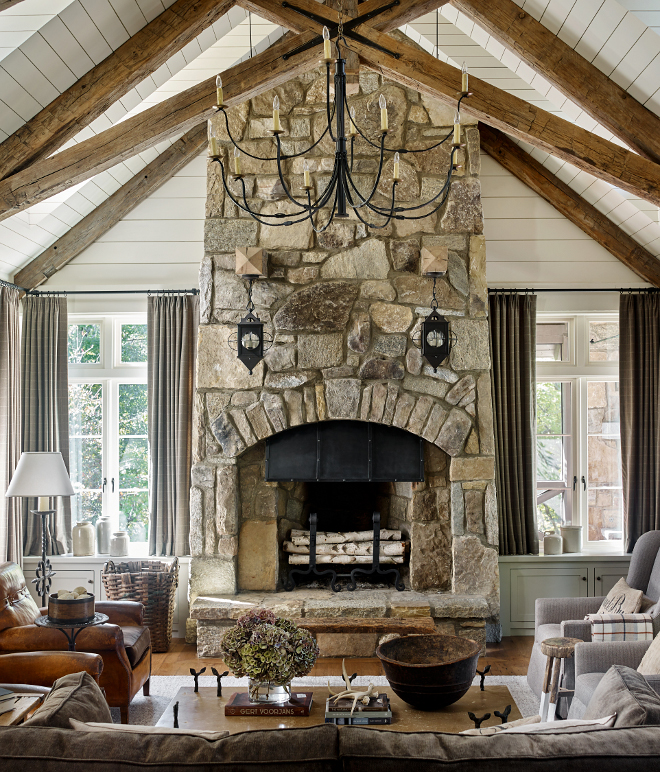 Stone Fireplace Stone Weathered Granite Stone Fireplace The fireplace design was inspired by an image the architect saw many years back in an old Arts and Crafts book Notice the two timbers projecting out of the fireplace where the sconces were hung #StoneFireplace #fireplace #WeatheredGranite