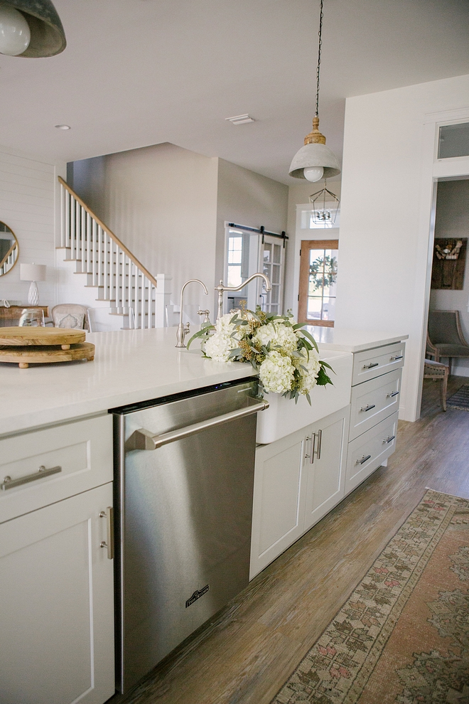 Light grey kitchen island with sink, marble-looking quartz countertop and brushed nickel pulls #kitchenisland #lihtgreyisland