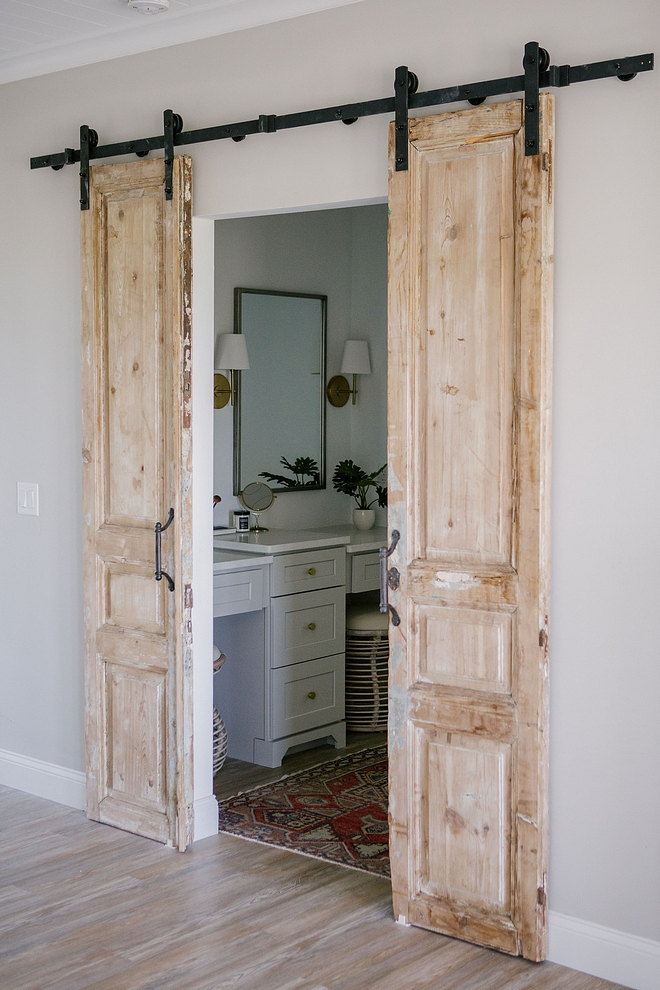 Hung on barn door hardware, these antique doors add personality and architectural interest to this bathroom #bathroom #antiquedoors #barndoor #bardoorhardware