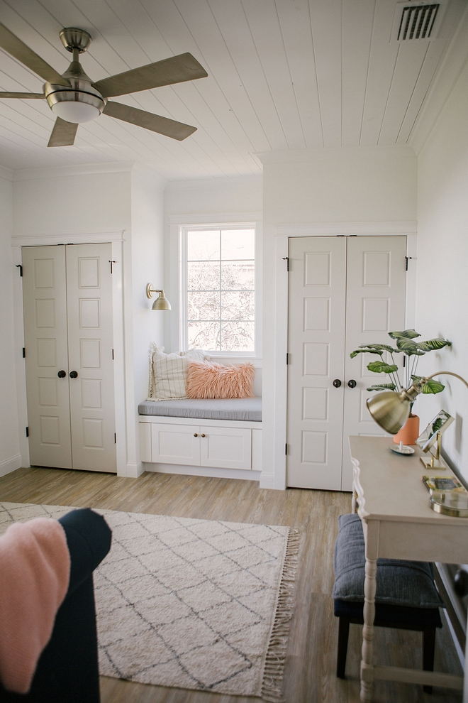 Closets, with greige doors, flank a window-seat