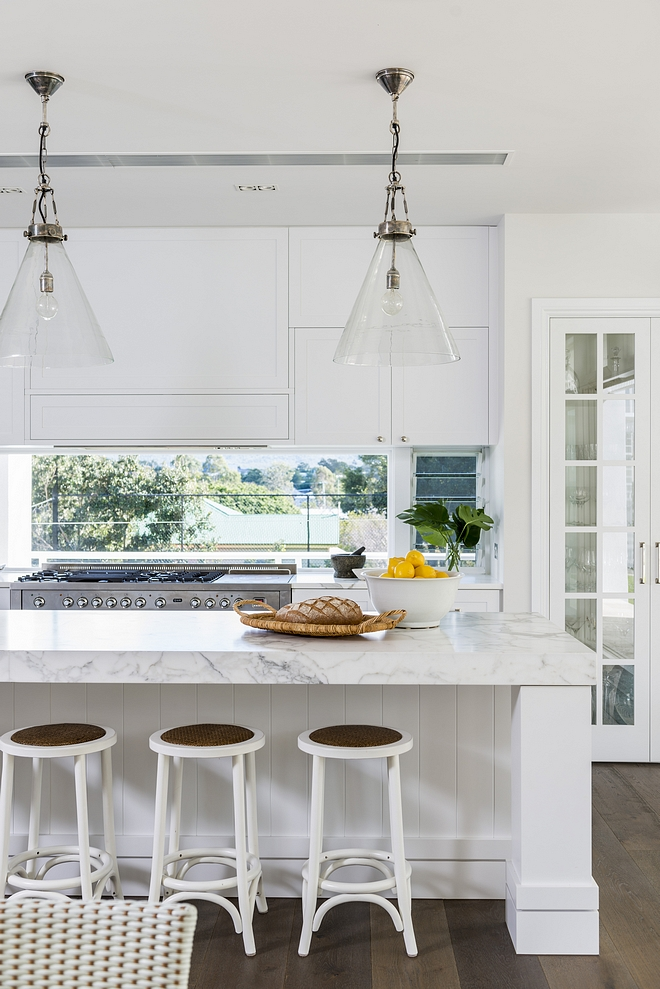 White kitchen with thick countertop and chunky island posts Glass windows behind the range gives an airy feel to this entire kitchen #kitchen #thickcountertop #chunkyislandposts