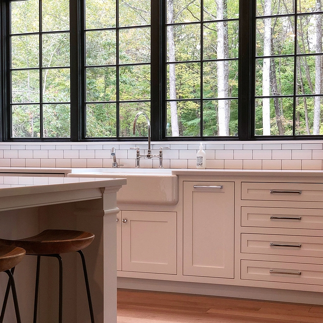 Benjamin Moore Chantilly Lace kitchen cabinet with Polished Chrome Hardware and black steel windows #BenjaminMooreChantillyLace #whitekitchen #ChromeHardware #blackwindows