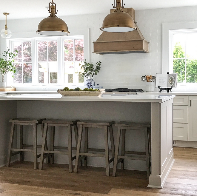 Coastal farmhouse kitchen with no upper cabinets and windows flanking range hood Grey kitchen island and chalk painted subway tile as backsplash #Coastalfarmhouse #kitchen #nouppercabinets #kitchenwindows #rangehood #chalkpaint #backsplash