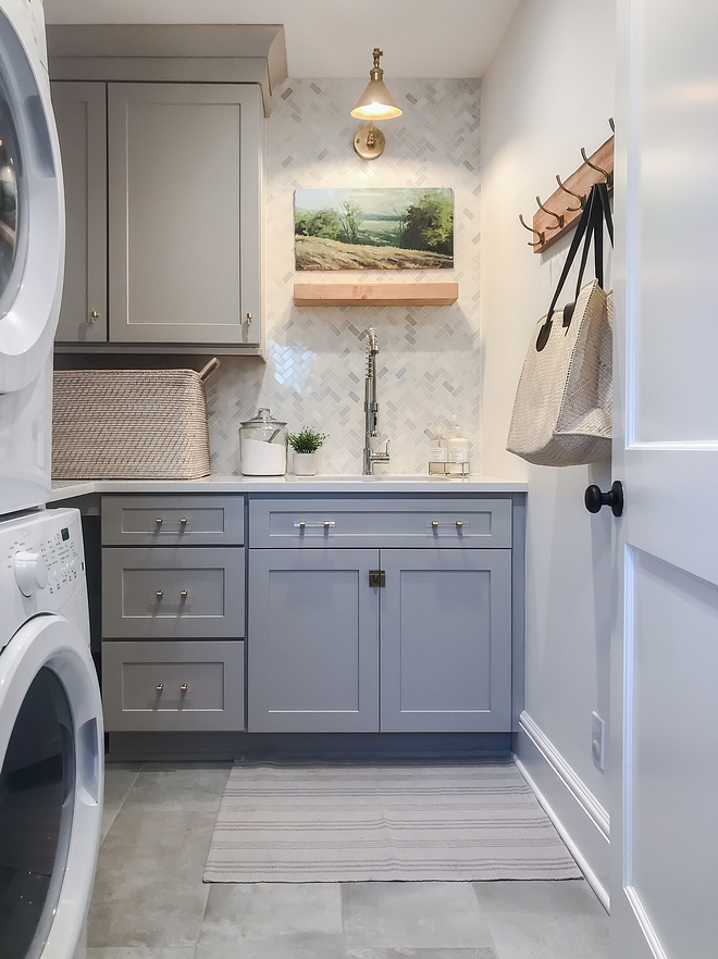 Grey Laundry room Grey cabinets works perfectly with the white marble quartz countertops and the white marble herringbone backsplash. Brass and acrylic hardware accentuates the shaker-style doors #greylaundryroom #greycabinet # greycabinets #marblequartz #countertop #marbleherringbonebacksplash #Brassandacrylichardware #shakerstyledoor