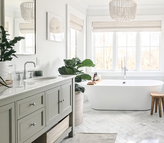 Bathroom featuring herringbone marble floor tile, white beaded chandelier over freestanding tub surrounded by windows dressed in white bamboo Roman shades #bathroom #herringbonemarbletile #whitebeadedchandelier #beadedchandelier #bambooromanshade #romanshade #freestandingtub #masterbathroom