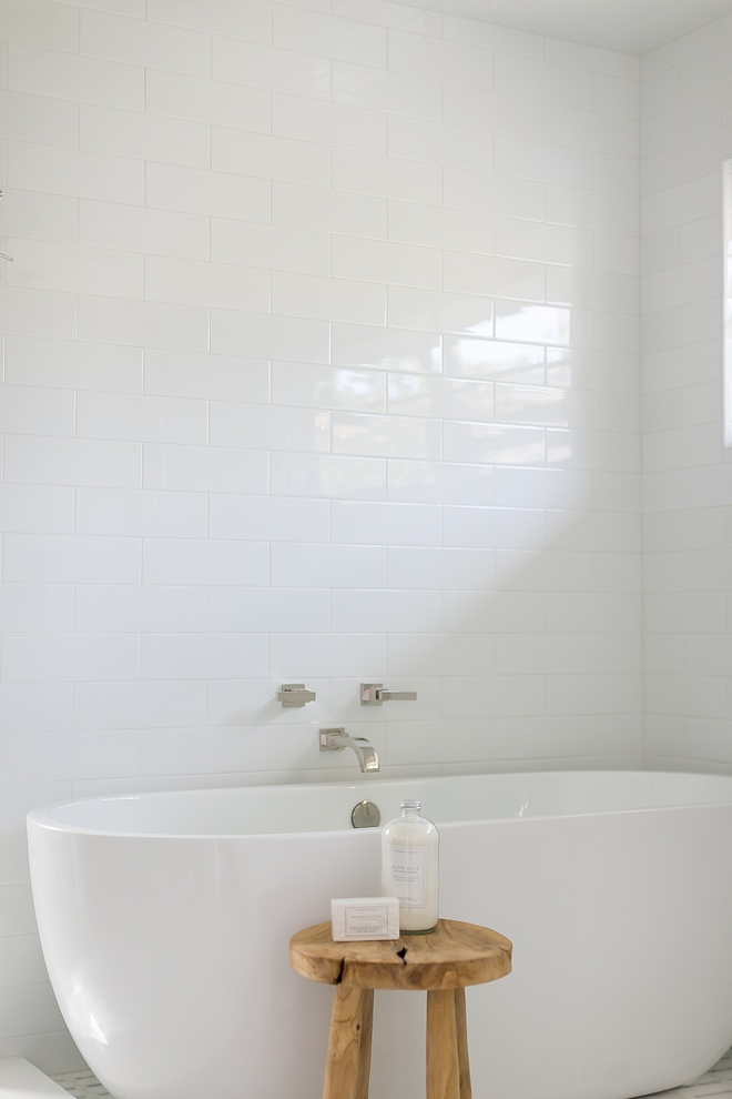 Simplicity is best when it comes to design bathrooms This spa-like bathroom features a sleek freestanding tub, a modern wall-mounted tub filler and large white subway tile on walls #bathroomdesign #bathroom #spabathroom