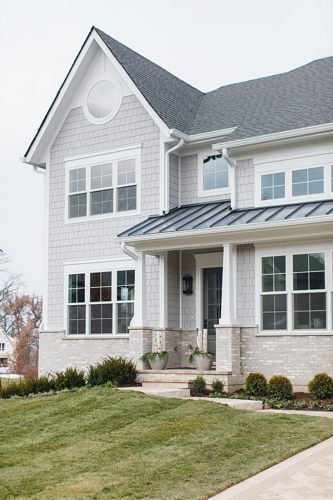 Exterior siding combination of grey shingles, white trim, white Craftsman style porch colums and brick accent Classic Exterior with light grey shingles and brick #Exterior #siding #greyshingles #whitetrim #Craftsmanstyleporchcolums #Craftsmancolumn #porch #brickexterior #brick #exteriorsiding