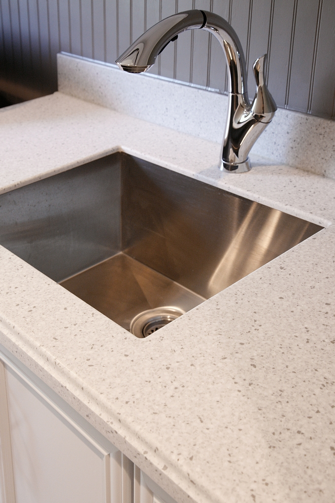 Laundry room countertop is Silver Birch ½' Corian with soft Ogee Edge. Backsplash is beadboard