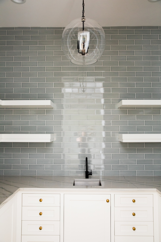 Pantry features a grey subway tile backsplash, white cabinets, brass knobs and floating shelvess #Butlerspantry #pantry #greysubwaytile