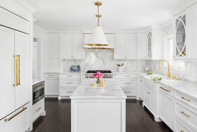 Classic white kitchen with white marble countertop white marble slab backsplash white cabinets white kitchen island and dark hardwood flooring #whitekitchen #whitekitchenisland #whitemarble