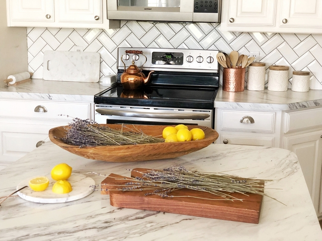 Backsplash is a subway tile with a beveled edge in a herringbone pattern The grout is light gray