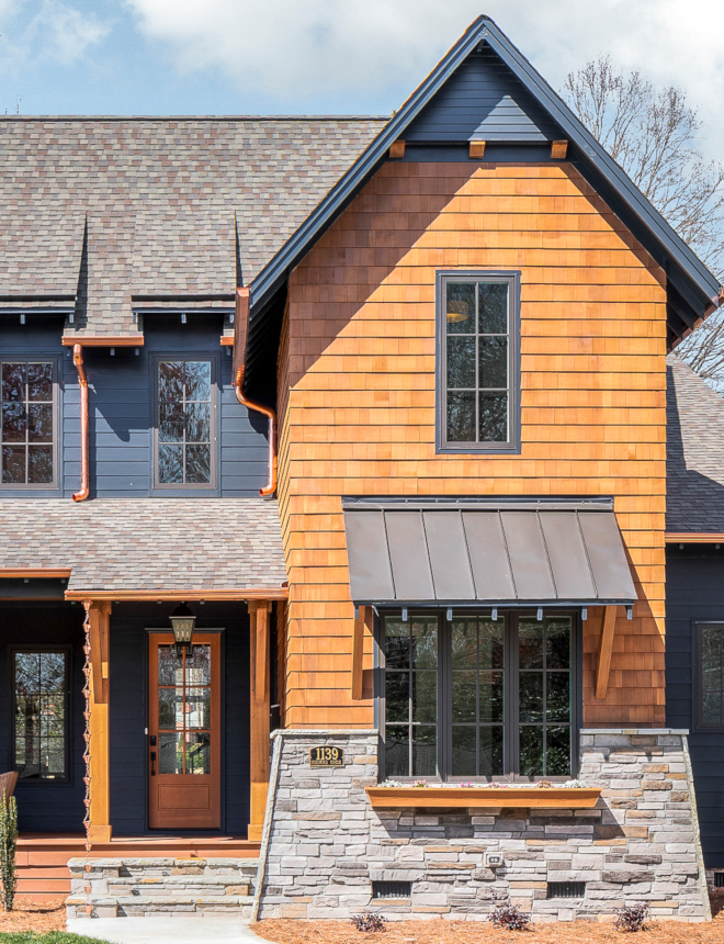 Dark Exterior Paint Color To lighten the facade up a bit and to ensure a focal point of the design, we used cedar shake and a stacked stone wing wall to coat the gabled bump out. A window box adds a feeling of quaintness and homeliness. The shake, as well as cedar columns, a front door are all stained in Benjamin Moore Hidden Valley #cedarshake #stackedstone #DarkExteriorPaintColor