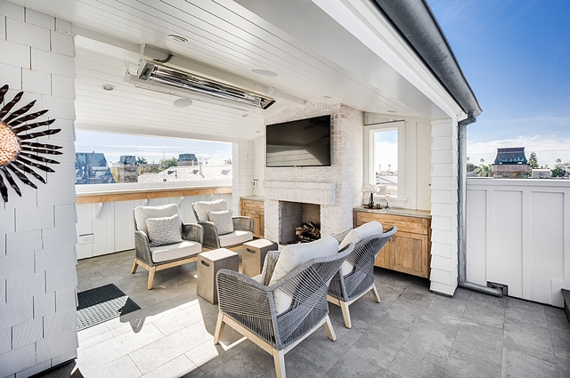 The rooftop features covered and non-covered areas, a TV, built-in bbq, under counter refrigerator, ice maker, sink, counterspace, sofa and lounging area, built-in fireplace #rooftop #decor #outdoors