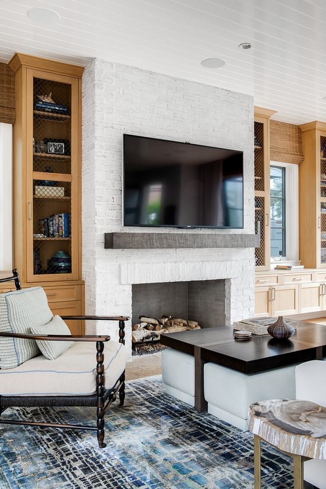 Living room features a stunning brick fireplace flanked by custom cabinets The cabinets are shaker style in rift white oak. Upper cabinets have wire mesh insert #Livingroom #brickfireplace #cabinets #shakerstylecabinet #Riftwhiteoak #wiremesh