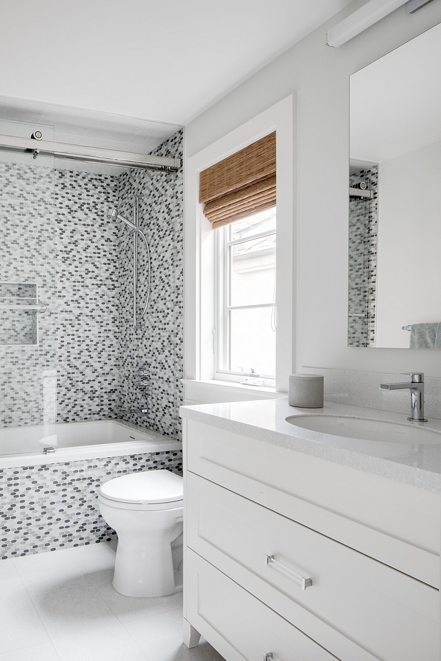 Bathroom This bathroom features a custom white vanity, painted in Benjamin Moore Atrium White and oval mosaic tile in shower and tub front #bathroom
