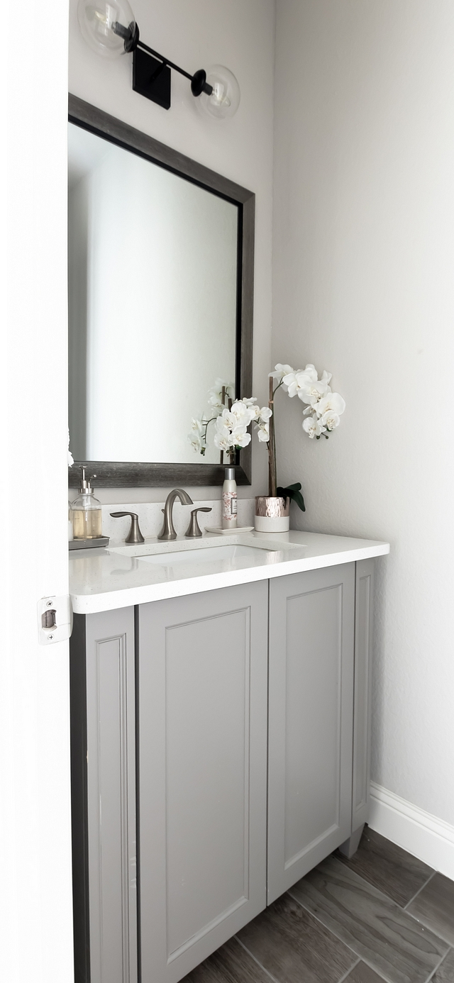 The powder room features a grey vanity, painted in Chandler Pewter #greyvanity #powderroom