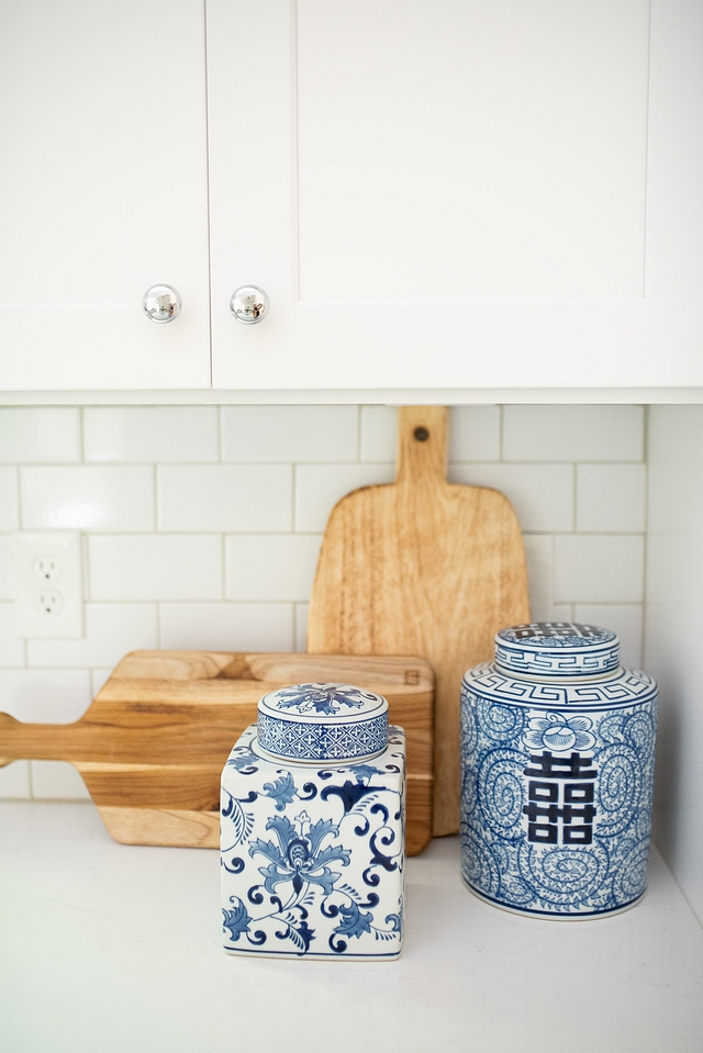 Kitchen Decor Kitchen countertop decor with blue and white ginger jars and wooden cutting boards on white quartz countertop and white subway backsplash White Cabinet paint color is SW Pure White