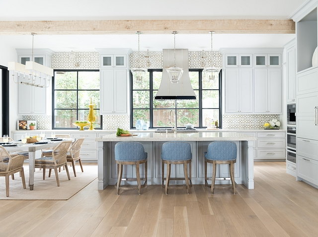 Metal-frame windows let sunlight wash over ceiling beams with a bleached finish that echoes wide-plank floors. Pale gray cabinetry and sandy-hue dining chairs, carpet, and tile further the bordering-on-beachy mood Kitchen #kitchen