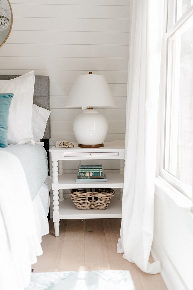 White nighstand Bedroom featuring white nighstand placed against a white shiplap wall and decorated with a white Ralph Lauren ceramic table lamp #Whitenighstand #Bedroom #nighstand #shiplap #RalphLauren #ceramictablelamp #tablelamp