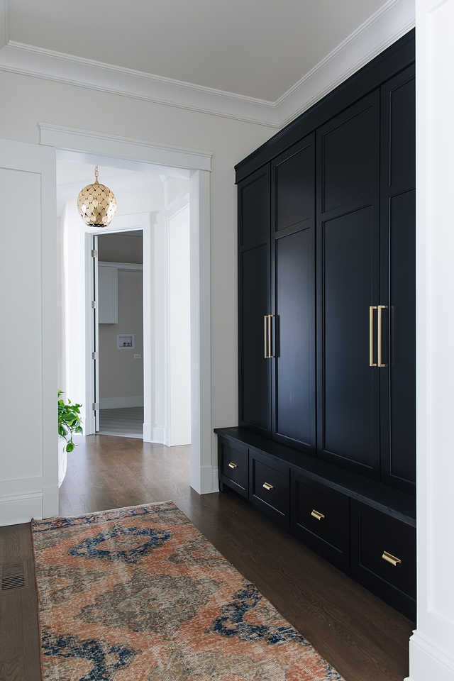 Black Mudroom Cabinet Black by Benjamin Moore The black mudroom cabinet is painted in Benjamin Moore Black and it features Honed Absolute Granite ledge Black cabinet with brass hardware #Blackmudroom #blackcabinet #blackpaintcolor #Blackcabinetwithbrass