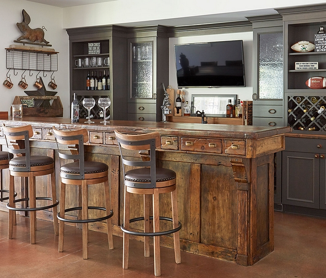 Rustic Wood Antique Bar with Gray Perimeter Cabinets The antique bar was locally sourced. The perimeter cabinets are alder with a flint finish and features seeded glass door inserts and built in wine storage #bar #cabinet #barcabinet #bardesign #barideas #winestorage #rusticinteriors #distressedcabinet #rusticcabinet