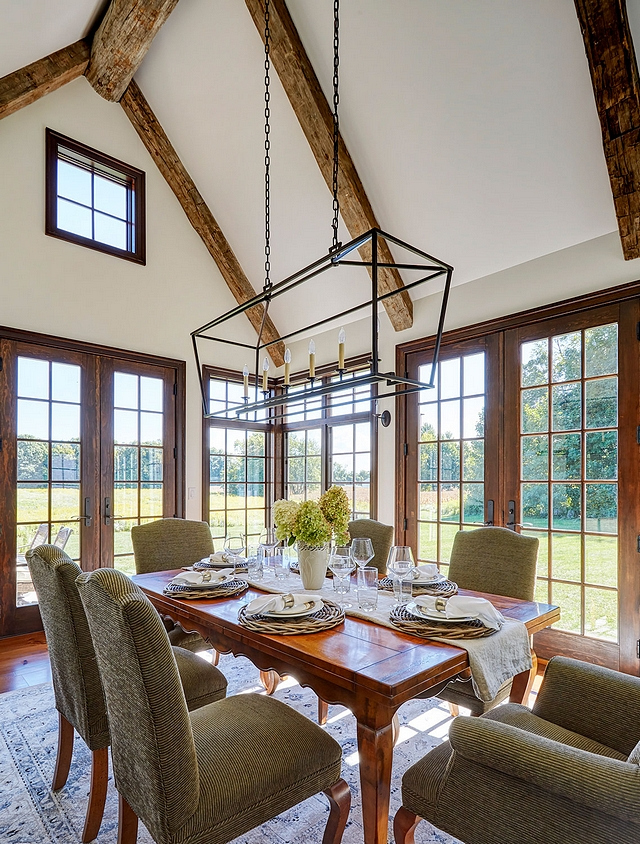 Dining Room Reclaimed wood beam Reclaimed hand hewn barn beams are used for the ridge beam in the vaulted dining room ceiling while floor-to-ceiling windows and French doors frame the country view #diningroom #reclaimedwoodbeam #beams #windows #ceiling #doors #diningroom