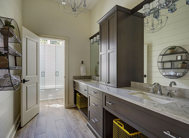 Bathroom features a neutral color scheme with warm white shiplap walls, dark wood vanity with his and her sinks and wood-looking porcelain floor tile #Bathroom #neutralcolor #colorscheme #shiplap #darkwoodvanity #woodlookingporcelaintile