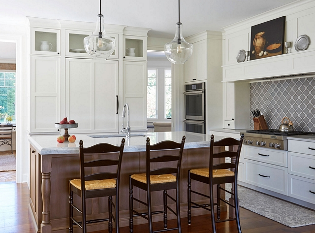 Classic white kitchen What a warm and inviting kitchen Classic white perimeter cabinets with shaker style doors contrast with a medium-stained wooden island #whitekitchen #classickitchen #interiordesign #warmwhitekitchen #kitchen #kitchenisland