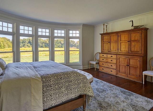 Master bedroom This inviting master bedroom a stunning curved wall of windows. Paint color is Sherwin Williams SW7014 Eider White in an Eggshell finish #masterbedroom #curvedwall