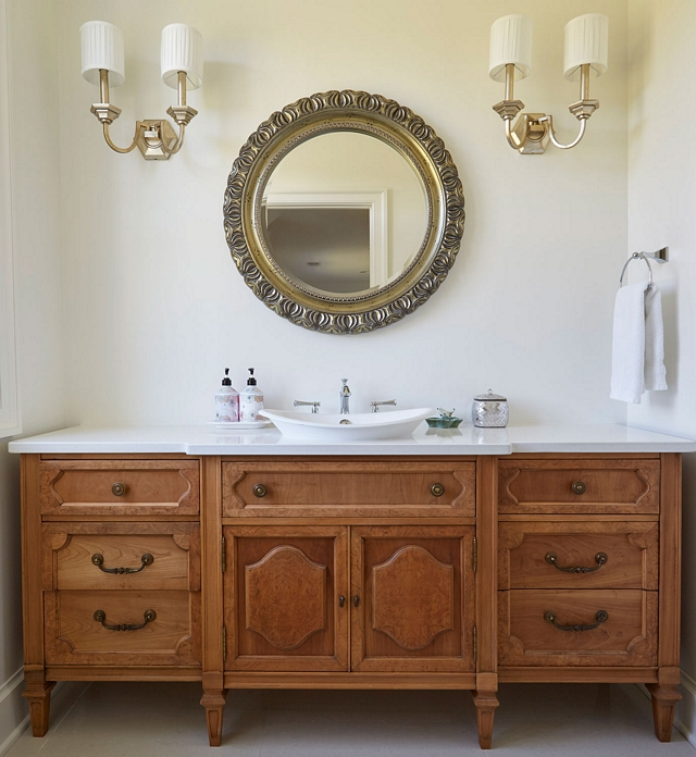 Furniture-like vanity cabinet This powder room features a beautiful furniture-like vanity cabinet with vessel sink, ornate mirror and matching sconces. Paint color is Sherwin Williams SW7014 Eider White in an Eggshell finish Furniture-like vanity cabinet #Furniturelikevanity #vanity #cabinet