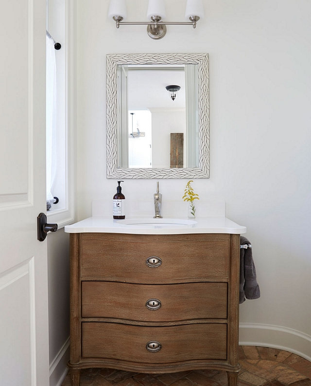 Powder room features a Restoration Hardware vanity and brick flooring