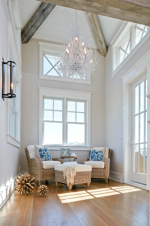 Small sitting room with tall ceiling featuring reclaimed beams, shiplap and a coastal white twig chandelier #sittingroom #smallspaces #ceilingbeams #coastalchandelier #twigchandelier #chandelier
