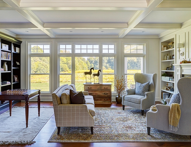 The kitchen opens to a cozy living room with coffered ceiling, wide plank pine flooring, and upholstered wingback chairs Wall color is Sherwin Williams Eider White #livingroom #cofferedceiling #SherwinWilliamsEiderWhite #livingroom